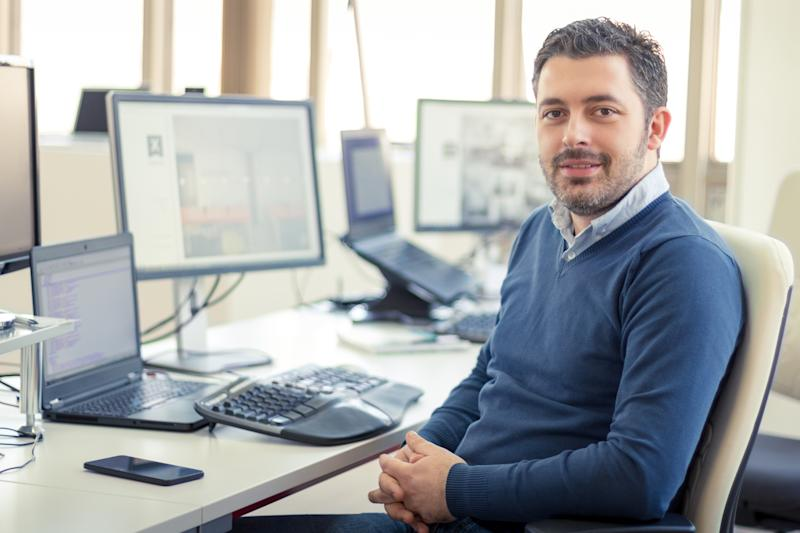 Man sitting at desk with computer, smiling