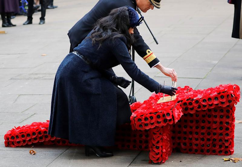 Duchess Meghan lays a Cross of Remembrance in front of wooden crosses from the Graves of Unknown British Soldiers from the First and Second World Wars, during her visit to the Field of Remembrance at Westminster Abbey in London on Nov. 7, 2019.