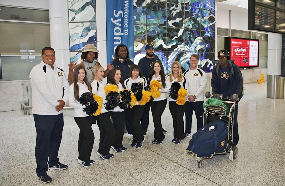 California Golden Bears cheerleaders welcome players as they arrive at Sydney International airport. (AP Photo/Rob Griffith)
