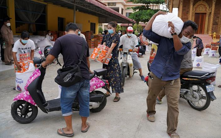 People carry sacks of rice and other food donated by the local government inside a red zone in Phnom Penh - Cindy Liu