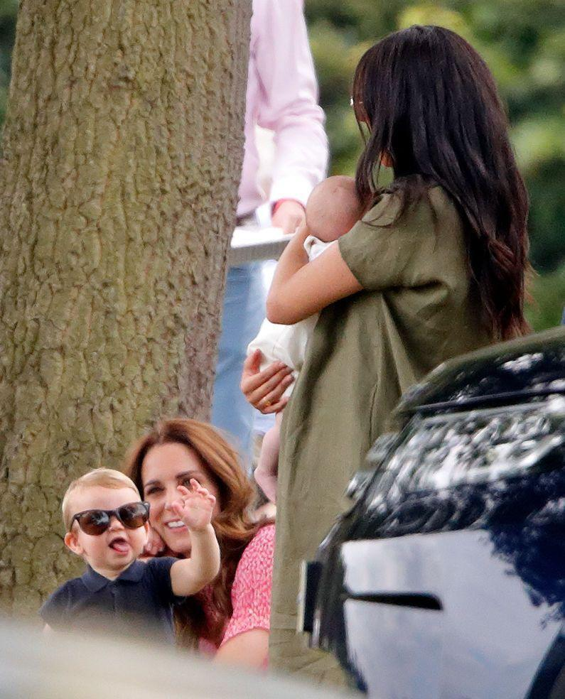 <p>Standing in front of Kate, Louis motions to his cousin Archie Mountbatten-Windsor, held by his mother Meghan Markle,</p>