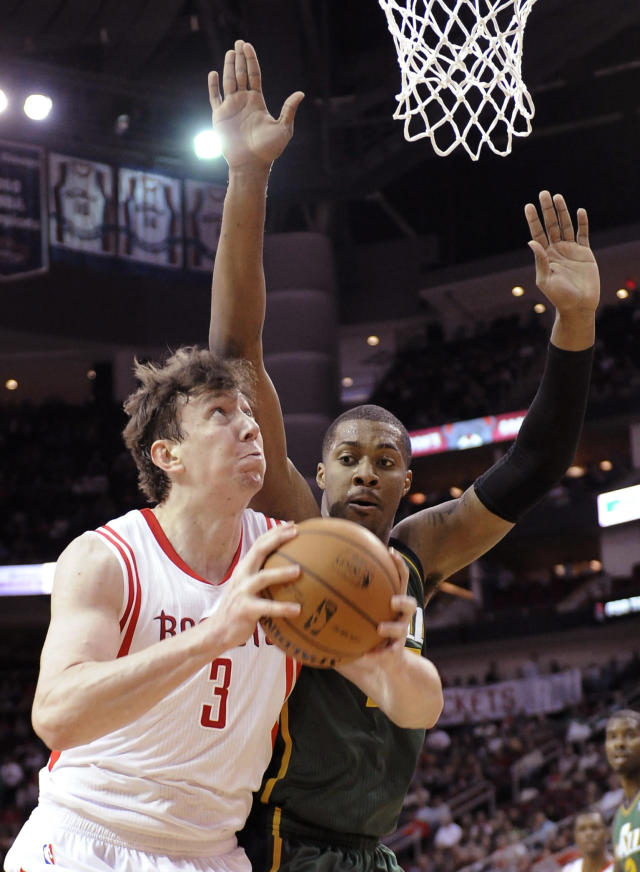Houston Rockets's Omer Asik (3) is pressured by Utah Jazz's Derrick Favors as he goes to the basket in the first half of an NBA basketball game Monday, March 17, 2014, in Houston. (AP Photo/Pat Sullivan)