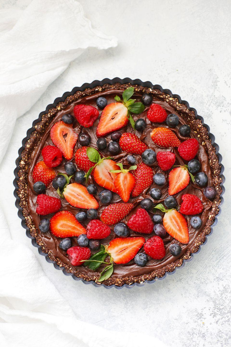 """<p>Need to impress a crowd? This chocolate berry tart is a guaranteed win, no oven required.<br></p><p><a class=""""link rapid-noclick-resp"""" href=""""https://www.onelovelylife.com/chocolate-berry-tart/"""" rel=""""nofollow noopener"""" target=""""_blank"""" data-ylk=""""slk:GET THE RECIPE"""">GET THE RECIPE</a></p><p><em>Per serving: 209 calories, 10.9 g fat, 28.1 g carbs, 77.7 mg sodium, 12.3 g sugar, 4.8 g fiber, 3.5 g protein</em></p>"""