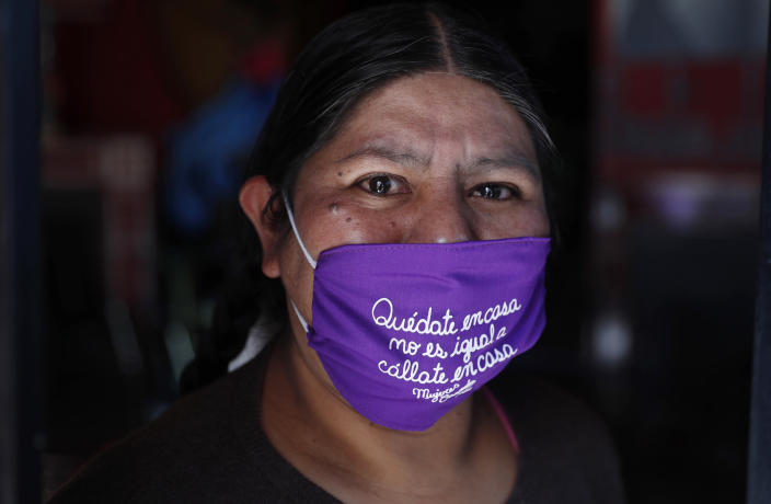 """Emiliana Quispe poses for a portrait wearing a face mask that reads in Spanish: """"Stay home. It's not the same as 'shut up at home,'"""" at the headquarters of the local feminist organization """"Mujeres Creando,"""" or Women Creating, where members are making the masks to sell amid the spread of the new coronavirus in La Paz, Bolivia, Friday, April 24, 2020. (AP Photo/Juan Karita)"""