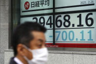 A man wearing a protective mask walks in front of an electronic stock board showing Japan's Nikkei 225 index at a securities firm Friday, Feb. 26, 2021, in Tokyo. Asian shares skidded Friday after rising bond yields triggered a broad sell-off on Wall Street that erased the markets gain for the week and handed the Nasdaq composite index its steepest loss since October. (AP Photo/Eugene Hoshiko)