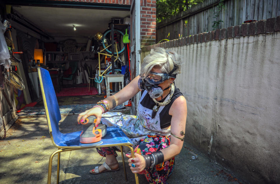 Rachel Berry works in the driveway to her garage studio, refinishing a chair she will turn into art, Monday, July 6, 2020, in New York. Before the coronavirus pandemic, Berry worked as a bartender and waited tables, jobs that gave her enough time to work on her creative pursuits. But as New York City tries to reopen, there's concern that jobs for the city's creative class are no longer readily available. (AP Photo/Bebeto Matthews)