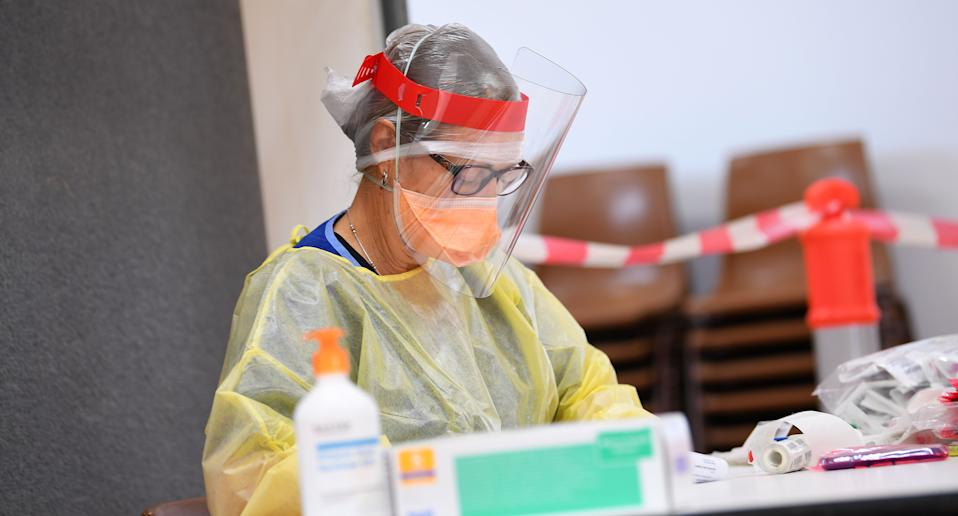A healthcare worker is seen at work at a pop-up Covid testing centre at the Kilmore Memorial Hall in Kilmore, Victoria. Source: AAP