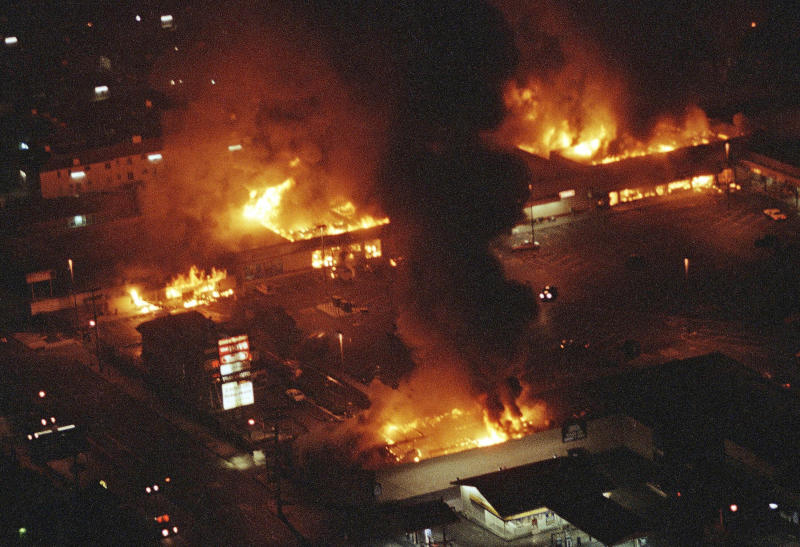 FILE - In this April 29, 1992 file photo, several buildings in a Boys Market shopping center are fully engulfed in flames before firefighters can arrive as rioting erupted in South-Central Los Angeles following the acquittal of four police officers in the videotaped beating of Rodney King.  (AP Photo/Reed Saxon, File)