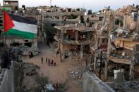 A Palestinian flag flies as the ruins of houses, which were destroyed by Israeli air strikes during the Israeli-Palestinian fighting, are seen, in Gaza