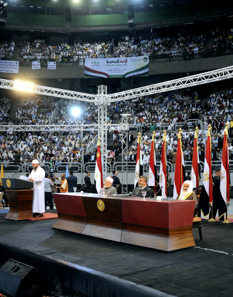 "In this image released by the Egyptian Presidency, Egyptian President Mohammed Morsi listens to a speaker at a rally called for by hardline Islamists loyal to the Egyptian president to show solidarity with the people of Syria, in a stadium in Cairo, Egypt, Sunday, June 15, 2013. Egypt's Islamist president announced Saturday that he was cutting off diplomatic relations with Syria and closing Damascus' embassy in Cairo, decisions made amid growing calls from hard-line Sunni clerics in Egypt and elsewhere to launch a ""holy war"" against Syria's embattled regime. (AP Photo/Egyptian Presidency)"