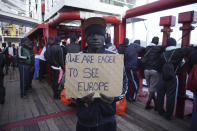 """A man shows a banner reading """"We are eager to see Europe"""" before disembarking from aboard the Ocean Viking ship as it reaches the port of Messina, Italy, Tuesday, Sept. 24, 2019. The humanitarian ship has docked in Italy to disembark 182 men, women and children rescued in the Mediterranean Sea after fleeing Libya. (AP Photo/Renata Brito)"""