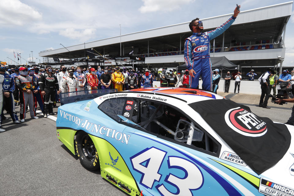 Driver Bubba Wallace takes a selfie with himself and other drivers that pushed his car to the front in the pits of the Talladega Superspeedway prior to the start of the NASCAR Cup Series auto race at the Talladega Superspeedway in Talladega Ala., Monday June 22, 2020. In an extraordinary act of solidarity with NASCAR's only Black driver, dozens of drivers pushed the car belonging to Bubba Wallace to the front of the field before Monday's race as FBI agents nearby tried to find out who left a noose in his garage stall over the weekend.  (AP Photo/John Bazemore)