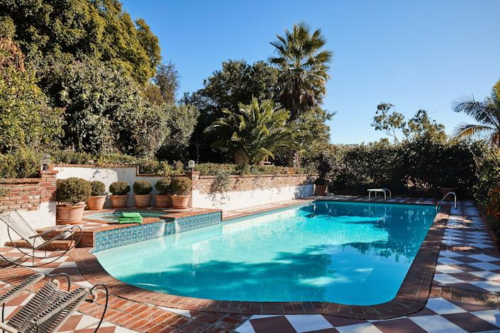 """<div class=""""caption""""> Dahan didn't have room in her budget for new outdoor tiles, so she painted the poolside cement with white paint to give the illusion of tilework. The pool's original diving board still launches guests into the water. </div>"""