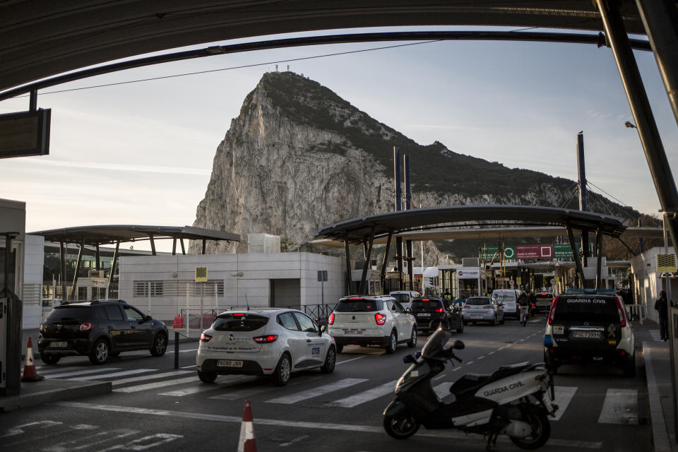 Cars queue to cross the border between Spain and Gibraltar, in La Linea de la Concepcion, Spain, Friday Jan. 31, 2020. Britain officially leaves the European Union on Friday after a debilitating political period that has bitterly divided the nation since the 2016 Brexit referendum. (AP Photo/Javier Fergo)