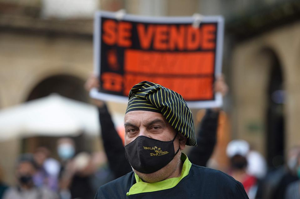 """A cook stands next to a """"For sale"""" sign during a protest in support of restaurants and bars and to demand changes in the strict time regulations amid the coronavirus pandemic in Ourense, northwestern Spain, on October 14, 2020.  (Photo by MIGUEL RIOPA/AFP via Getty Images) (AFP via Getty Images)"""