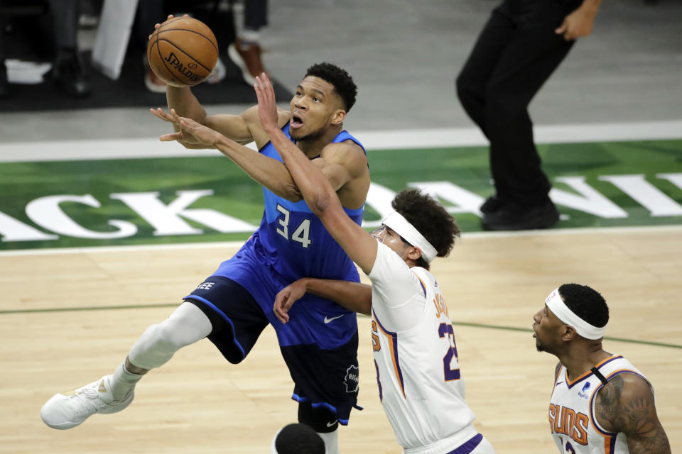 Milwaukee Bucks Giannis Antetokounmpo, left, drives to the basket against Phoenix Suns' Cameron Johnson, center, during the first half of an NBA basketball game Monday, April 19, 2021, in Milwaukee. (AP Photo/Aaron Gash)