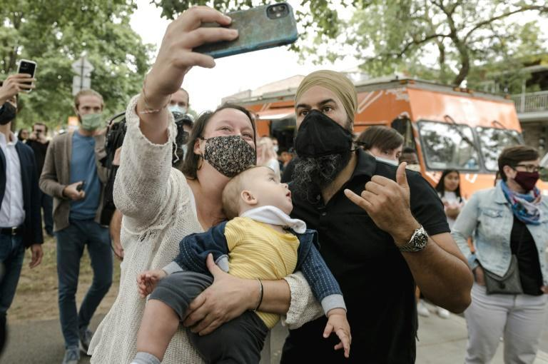 A baby looks at NDP leader Jagmeet Singh as he takes a selfie with a constituant in Montreal after he served his own twist on poutine, Quebec's signature delicacy to voters ahead of the September 20 election (AFP/Andrej Ivanov)