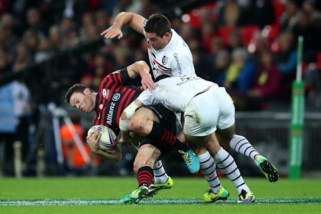 LONDON, ENGLAND - OCTOBER 18: Duncan Taylor of Saracens is tackled by Jean-Marc Doussain and Florian Fritz of Toulouse during the Heineken Cup pool three match between Saracens and Toulouse at Wembley Stadium on October 18, 2013 in London, England. (Photo by David Rogers/Getty Images)