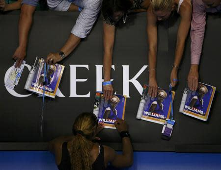Serena Williams of the United States signs autographs for fans after defeating Ashleigh Barty of Australia in their women's singles match at the Australian Open 2014 tennis tournament in Melbourne January 13, 2014. REUTERS/David Gray