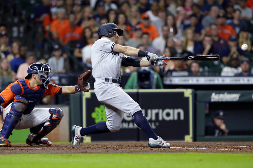 New York Yankees' Gio Urshela hits a two-run single in front of Houston Astros catcher Jason Castro during the fourth inning of a baseball game Friday, July 9, 2021, in Houston. (AP Photo/Michael Wyke)