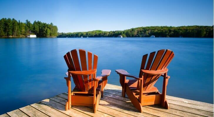 Two Adirondack chairs on a lakeside dock