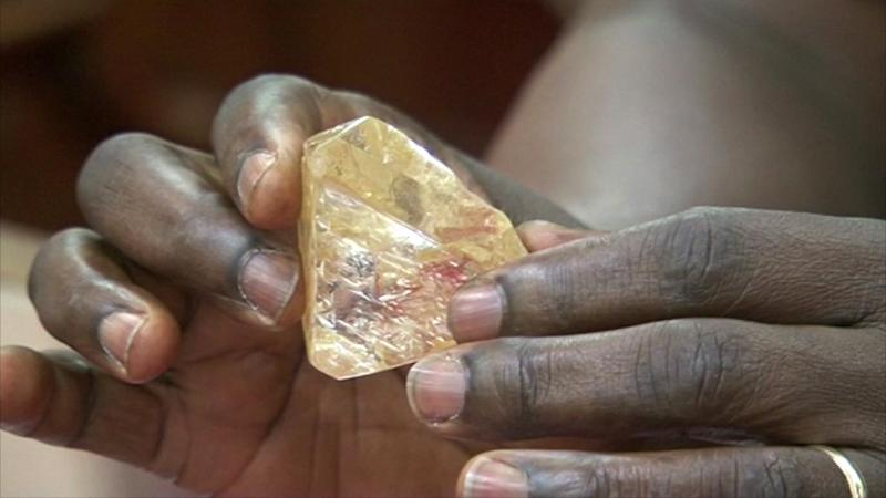 In this photo taken from video footage, Sierra Leone's President Ernest Bai Koroma hands a diamond during a meeting with delegates of Kono district, where the gem was found, at the presidential office in Freetown, Sierra Leone, Thursday, March 16, 2017. A pastor in Sierra Leone has discovered the largest uncut diamond found in more than four decades in this West African country and has turned it over to the government, saying he hopes it helps to boost recent development in his impoverished nation. (SLBC via AP)