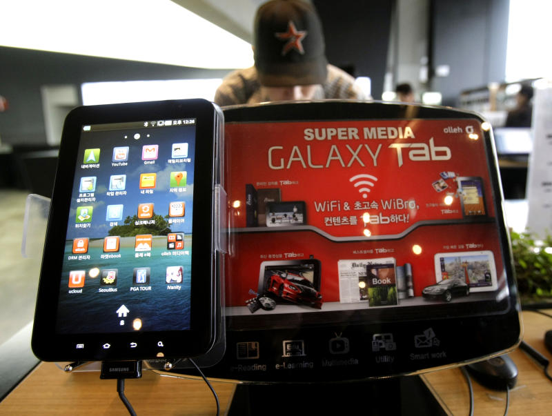 Samsung Electronics' Galaxy Tab, left, is displayed with at an advertising board, at the headquarters of South Korean mobile carrier KT in Seoul, South Korea, Friday, April 22, 2011. South Korea's Samsung Electronics Co. says it sued Apple Inc. for patent rights violations, only days after Apple sued Samsung for the same reason.(AP Photo/Ahn Young-joon)