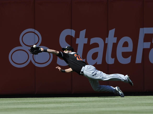 Miami Marlins' Justin Ruggiano catches a ball hit deep to center field by Philadelphia Phillies' Chase Utley (26) inning of an MLB National League baseball game on Sunday, May 5, 2013, in Philadelphia. (AP Photo/Michael Perez)