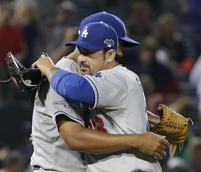 Los Angeles Dodgers relief pitcher Kenley Jansen (74) and Adrian Gonzalez (23) embrace after Game 1 of the National League Division Series against the Atlanta Braves, Friday, Oct. 4, 2013, in Atlanta. The Dodgers won 6-1.(AP Photo/John Bazemore)
