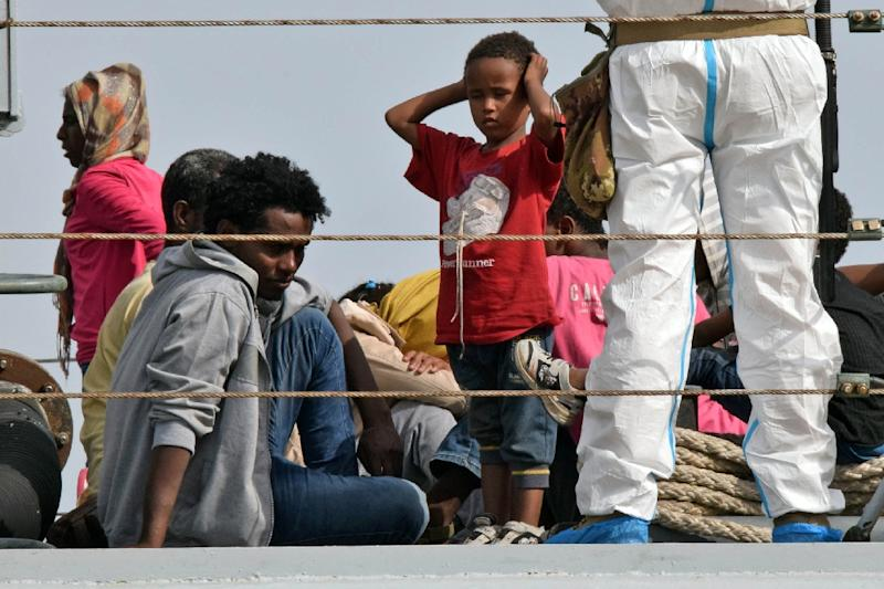 """Migrants disembark from the Italian military ship """"Sfinge"""" in the port of Augusta, on the eastern coast of Sicily on May 21, 2015 (AFP Photo/Giovanni Isolino)"""