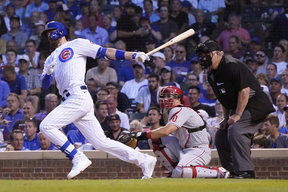 Chicago Cubs' Kris Bryant hits an RBI single off Philadelphia Phillies starting pitcher Aaron Nola as catcher J.T. Realmuto and home plate umpire Joe West watch during the third inning of a baseball game Tuesday, July 6, 2021, in Chicago. Rafael Ortega scored on the play. (AP Photo/Charles Rex Arbogast)