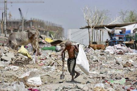 A boy looks for scrap metal using an improvised magnetic tool near a construction site in New Delhi