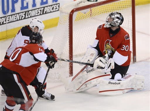 Ottawa Senators goalie Robin Lehner reacts as he is hit with the stick of New Jersey Devils center Harri Pesonen under pressure from Ottawa Senators' Mike Lundin during second period NHL action in Ottawa, on Monday March 25, 2013. (AP Photo/The Canadian Press, Adrian Wyld)