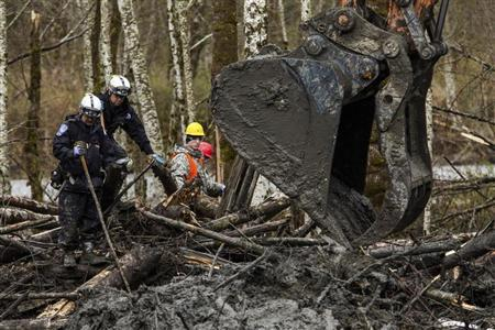 Rescuers watch carefully as an excavator combs through the large debris pile left by a mudslide in Oso, Washington, April 4, 2014. REUTERS/Max Whittaker