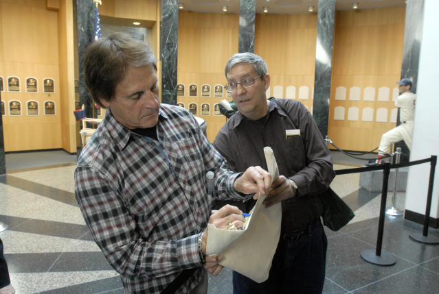 Baseball Hall of Fame inductee Tony La Russa, left, signs an autograph for a man who declined to be identified at the National Baseball Hall of Fame and Museum in Cooperstown, N.Y., Thursday, April 10, 2014. La Russa is scheduled to be inducted into the hall this summer. (AP Photo/Tim Roske)