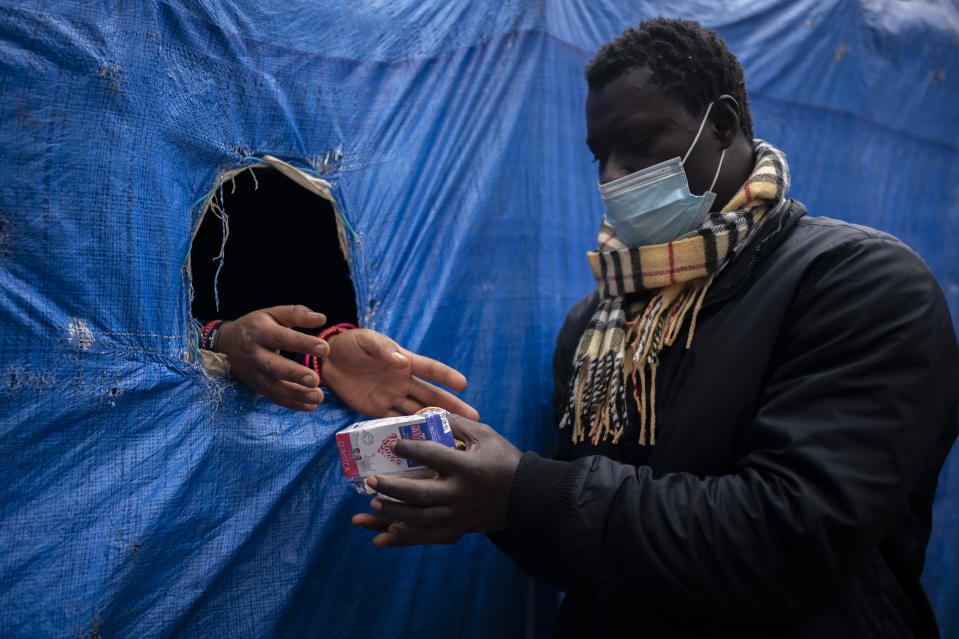 A migrant receives donated food outside Las Raices camp in San Cristobal de la Laguna, in the Canary Island of Tenerife, Spain, Saturday, March 20, 2021. While Spain has been critical of its European neighbours' lack of solidarity when it comes to sharing the responsibility of migration, the country is similarly being criticized by migrants, authorities and human rights organizations on the Canary Islands where some 23,000 people arrived by sea last year and where many thousands remain on the island forcefully. (AP Photo/Joan Mateu)