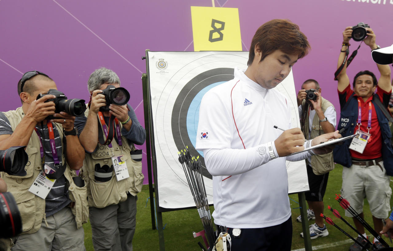 South Korea's Im Dong-hyun tallies his score during an individual ranking round at the 2012 Summer Olympics, Friday, July 27, 2012, in London. Dong-hyun set a world record in the round with a 699 score. (AP Photo/Marcio Jose Sanchez)