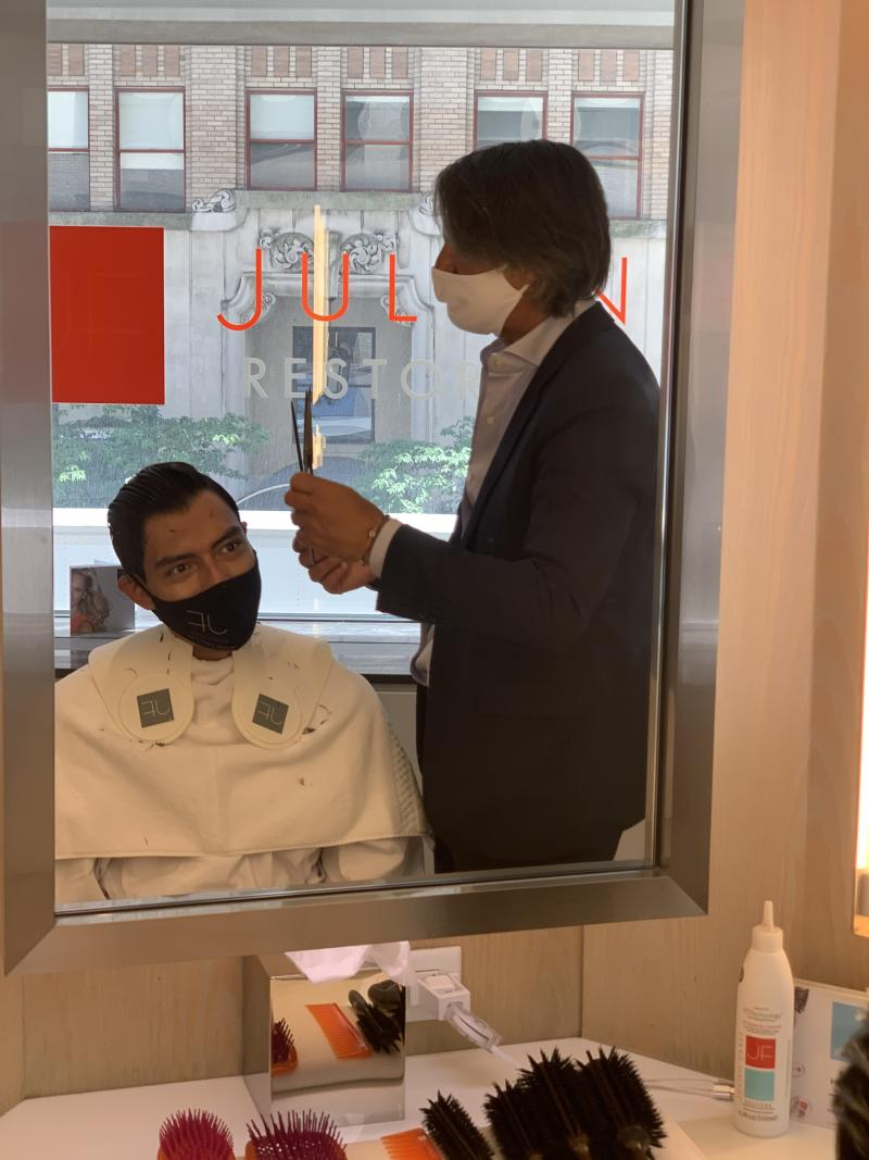 Julien Farel cuts a client's hair in his salon; newly reopened from coronavirus closure.