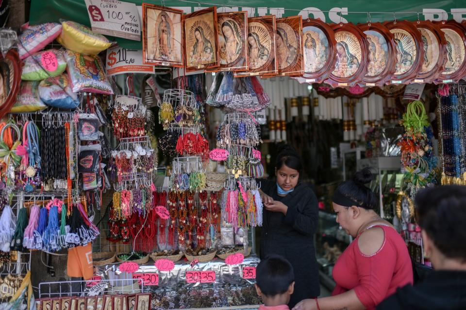 A woman sells religious images near the basilica of Guadalupe in Mexico City, on March 20, 2020. - Mexicans use religious images as shields against the new coronavirus, COVID-19. (Photo by PEDRO PARDO / AFP) (Photo by PEDRO PARDO/AFP via Getty Images)