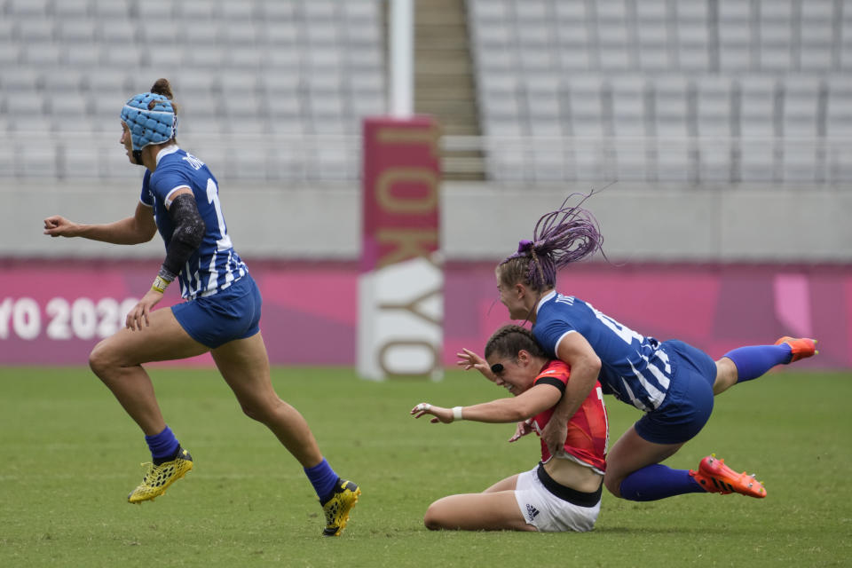 Britain's Helena Rowland, bottom, gets tackled by Russian Olympic Committee's Alena Tiron, in their women's rugby sevens match at the 2020 Summer Olympics, Thursday, July 29, 2021 in Tokyo, Japan. (AP Photo/Shuji Kajiyama)