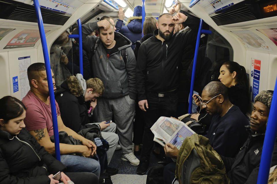 FILE - In this March 17, 2020 file photo people on a busy tube train at rush hour despite Prime Minister Boris Johnson calling on people avoid all non-essential contacts and travel, in London. More than 100,000 people have died in the United Kingdom after contracting the coronavirus. That's according to government figures released Tuesday Jan. 26, 2021. (Ian Hinchliffe/PA via AP, File)