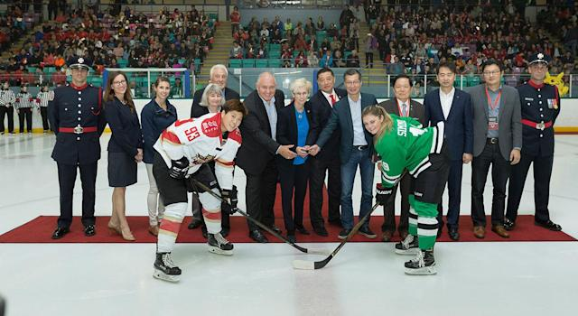 Players and management pose during the ceremonial puck drop before Kunlun's inaugural game in Markham, Ont. (Chris Tanouye/CWHL)