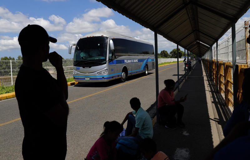 Honduran migrant Jose Maria Dubon Gutierrez, left, waits at a border crossing between Guatemala and Mexico for his family's turn to show Mexican immigration officers their documents after securing legal permission to stay in Mexico's southern states, near Ciudad Hidalgo, Mexico, Thursday, June 6, 2019. Behind, a bus passes, which local authorities say carry Central American migrants back to Guatemala, one day after Mexican police and immigration agents blocked the advance of about 1,000 Central American migrants who were walking along a highway. (AP Photo/Marco Ugarte)