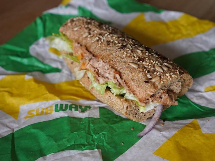 tuna sandwich with lettuce and tomato on wrapper paper