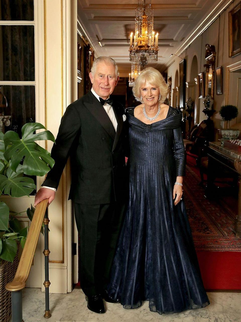 """<p>Clarence House released a new photo of Prince Charles and Camilla <a href=""""https://www.townandcountrymag.com/society/tradition/g25058013/prince-charles-70th-birthday-party-photos/"""" rel=""""nofollow noopener"""" target=""""_blank"""" data-ylk=""""slk:at the prince's 70th birthday celebration"""" class=""""link rapid-noclick-resp"""">at the prince's 70th birthday celebration</a>, which was held at Buckingham Palace. The Duchess of Cornwall is wearing a navy gown by Bruce Oldfield.</p>"""