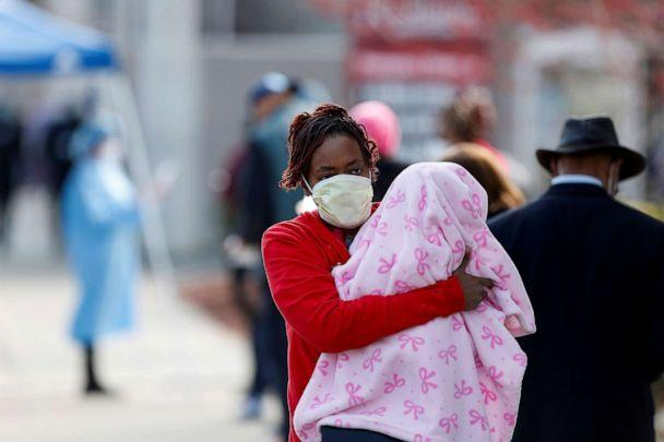 PHOTO: A woman holds a child at a testing site for COVID-19 outside Roseland Community Hospital in Chicago, April 7, 2020. (Joshua Lott/Reuters, File)