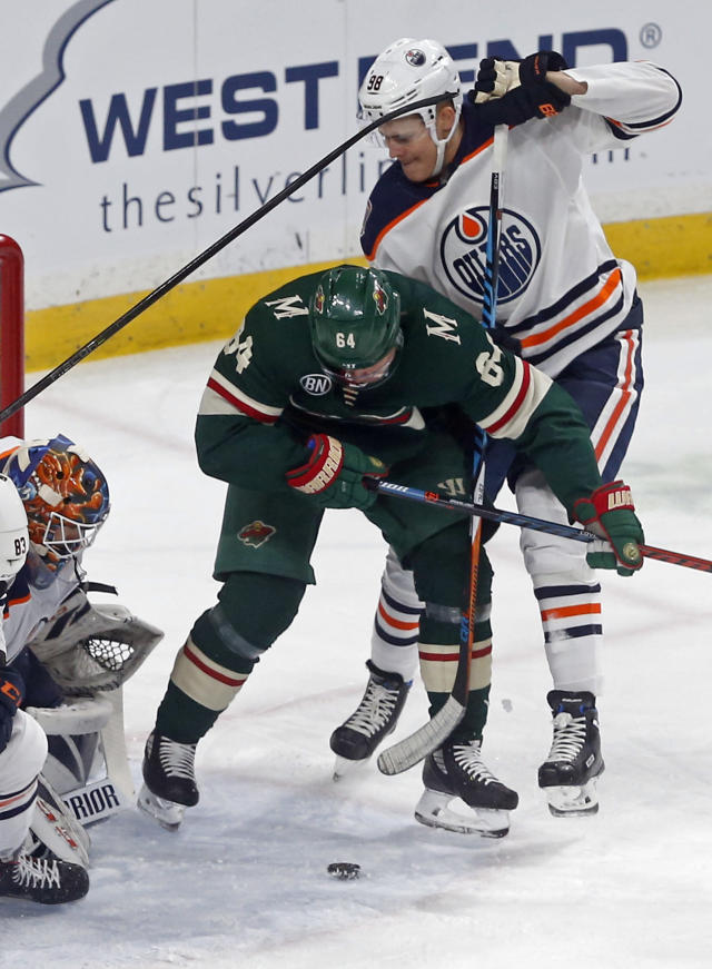 Edmonton Oilers' goalie Cam Talbot, lower left, looks on as Jesse Puljujarvi, right, of Sweden, defends against Minnesota Wild's Mikael Granlund of Finland during the first period of an NHL hockey game Thursday, Feb. 7, 2019 in St. Paul, Minn. (AP Photo/Jim Mone)