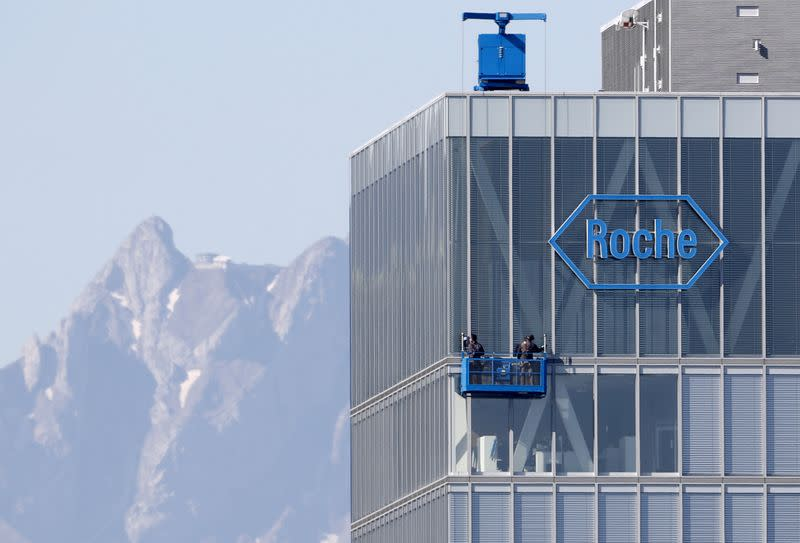FILE PHOTO: Workers clean windows of a building of Roche in Rotkreuz