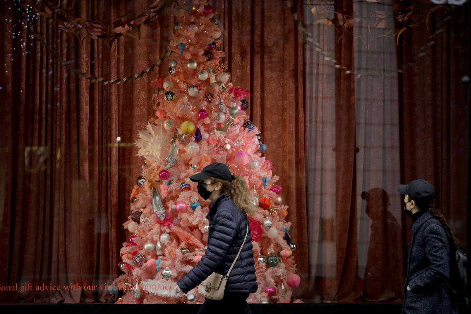 Women wearing face masks walk past a Christmas tree in the window of the Selfridges department store on Oxford Street, which is temporarily closed for in-store browsing with online collection possible from a collection point, during England's second coronavirus lockdown, in London, Monday, Nov. 23, 2020. British Prime Minister Boris Johnson has announced plans for strict regional measures to combat COVID-19 after England's second lockdown ends Dec. 2, sparking a rebellion by members of his own party who say the move may do more harm than good. (AP Photo/Matt Dunham)