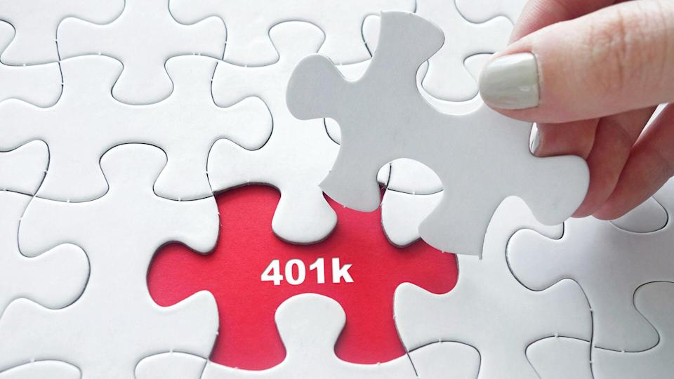 Close up of girl's hand placing the last jigsaw puzzle piece with word 401k.